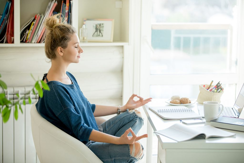 Portrait of an attractive woman in a chair at the table with cup and laptop, book, pencils, notebook on it. Lotus pose, concept photo
